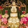 کیک چند طبقه سفید و طلایی همراه با گل ارایی میز مناسب جشنهای نامزدی، عروسی و سالگرد