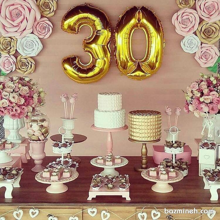 دکوراسیون تولد سی سالگی شامل دیزاین میز کیک و شیرینی، بادکنک های هلیومی و گلهای کاغذی