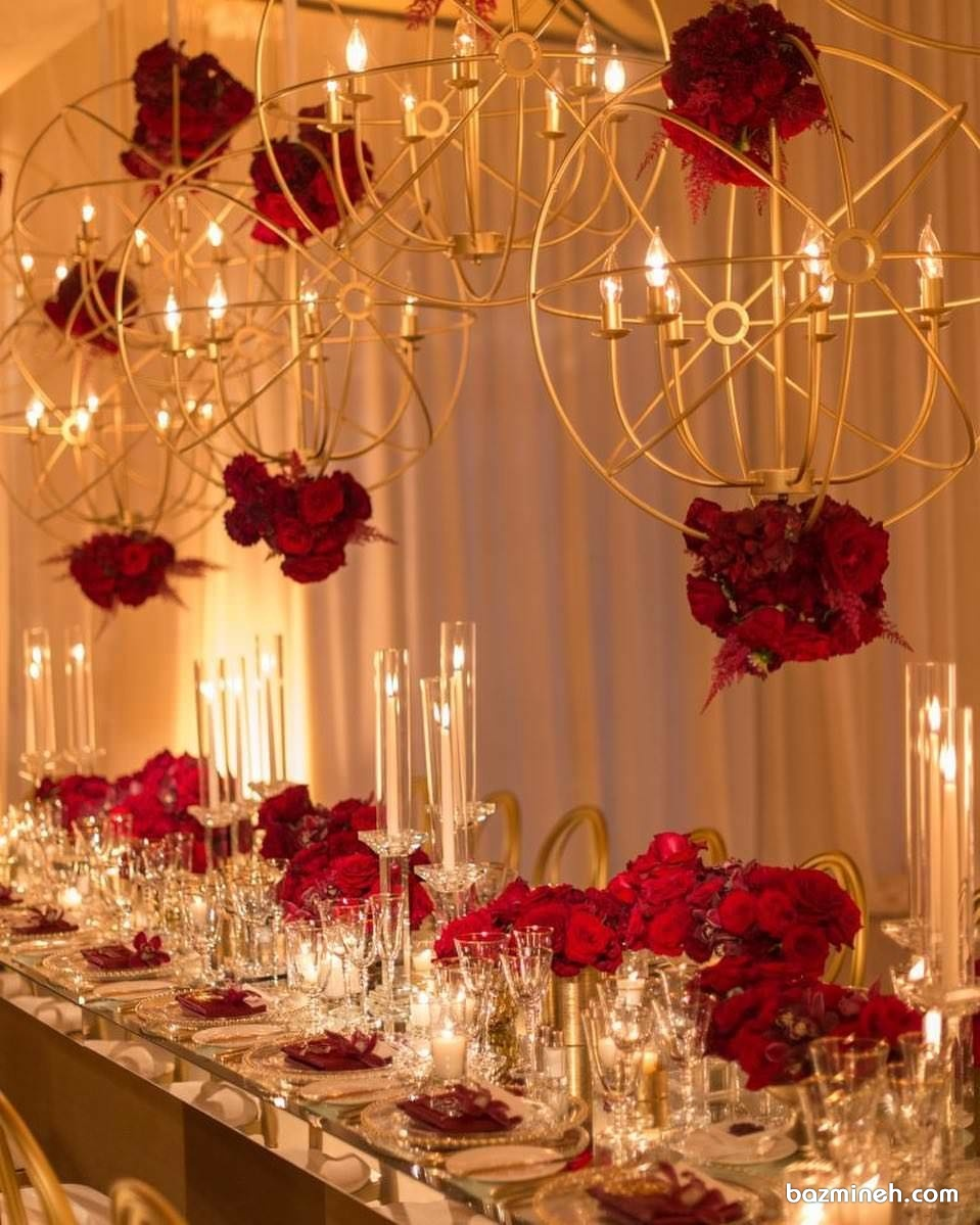 دیزاین میز جشن عروسی با گل های رز قرمز و شمع همراه با گل آرایی لوسترهای طلایی