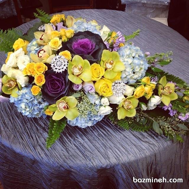 گل رومیزی میزهای پذیرایی مجالس باشکوه با گل های زرد و بنفش