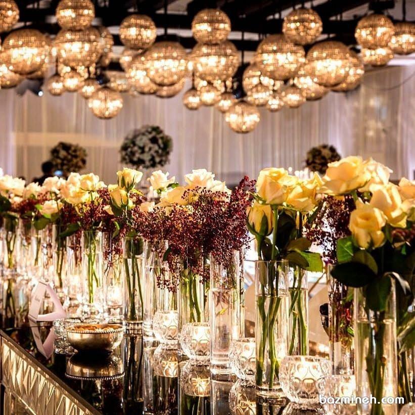 گل آرایی و شمع آرایی شیک میز مجالس باشکوه با گل های رز زرد و جاشمعی های کریستالی