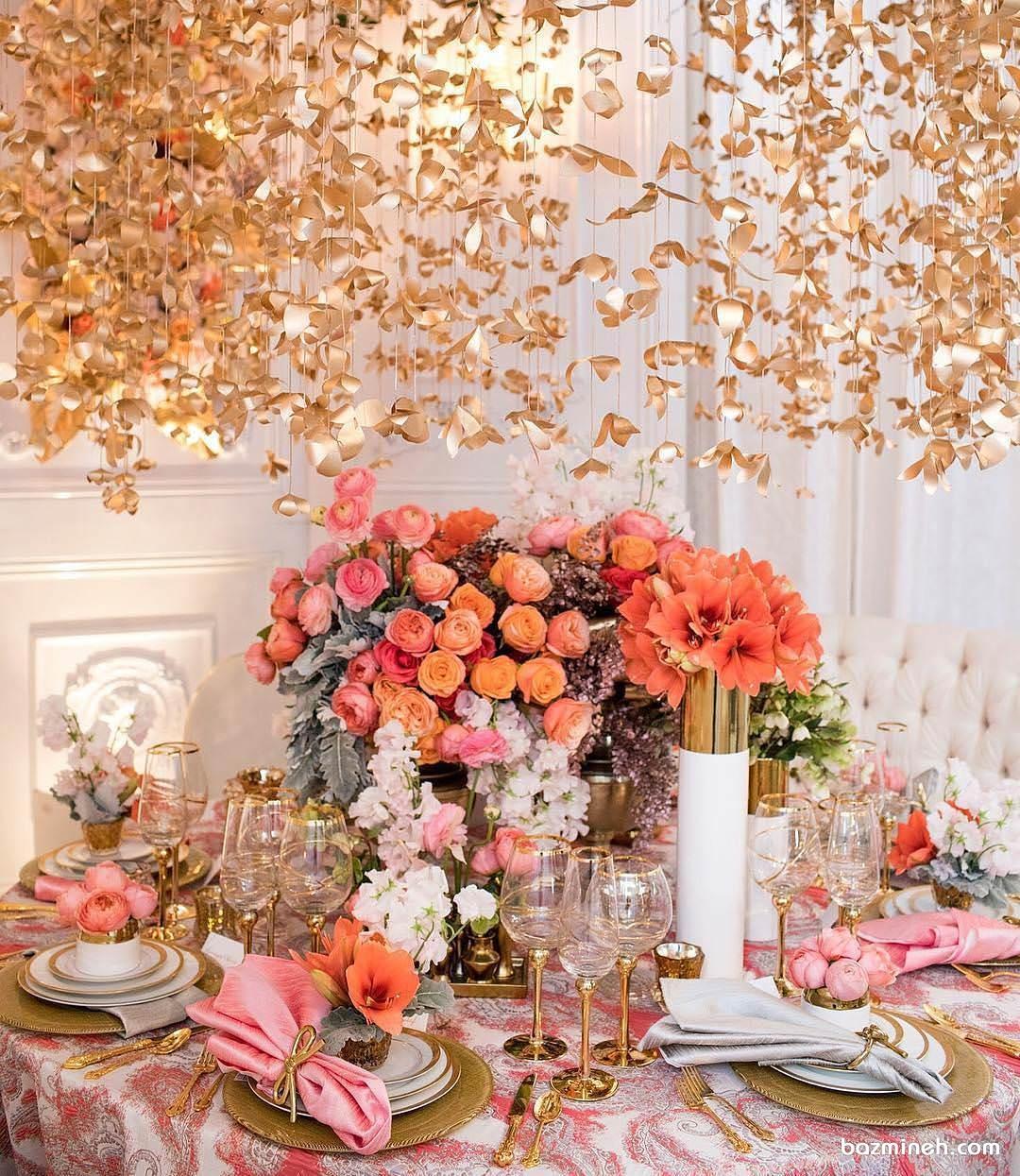 دیزاین شیک میز پذیرایی مجالس باشکوه با گل های طبیعی نارنجی و گل های کاغذی طلایی