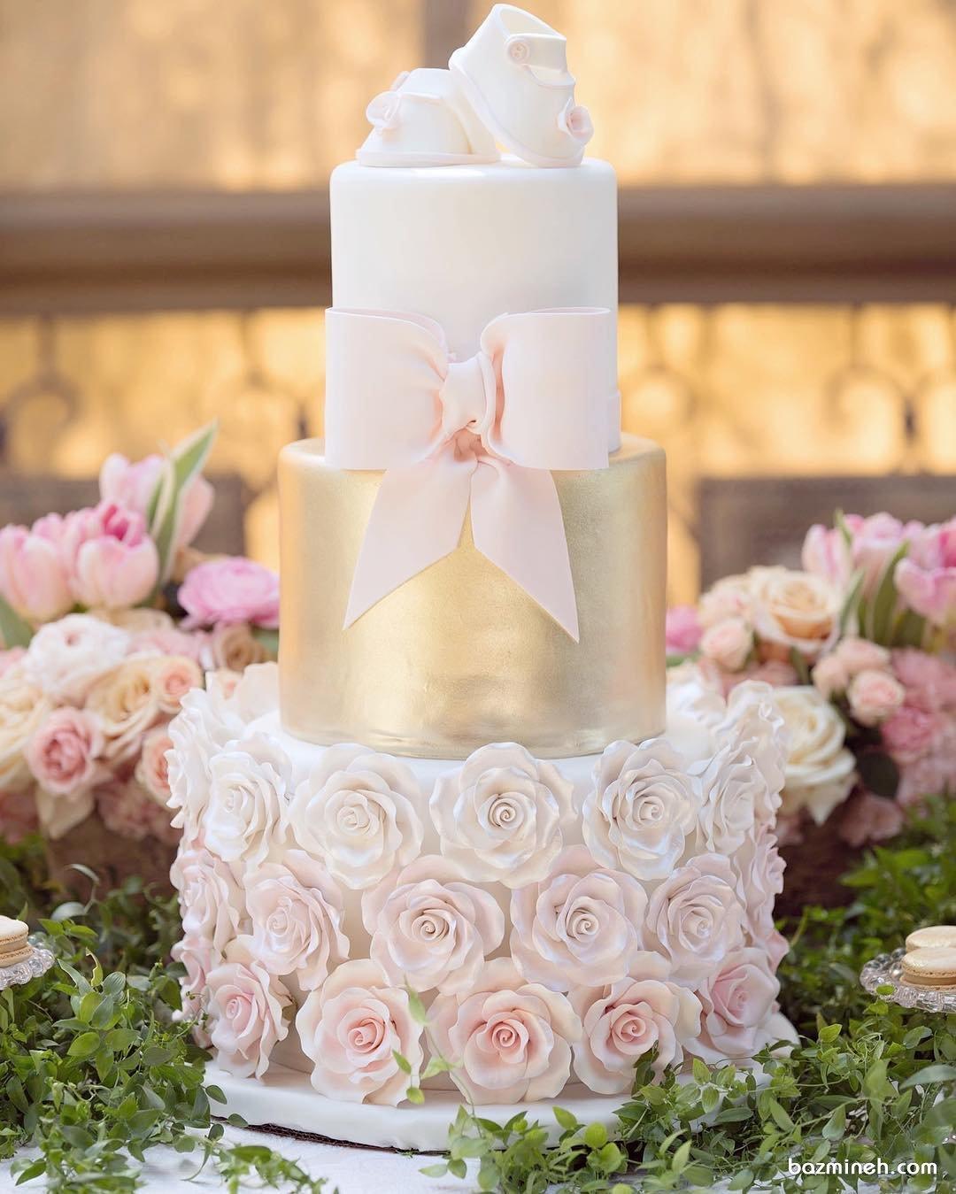 کیک خوشگل جشن بیبی شاور دخترانه تزئین شده با گل و پاپیون و کفش نوزادی
