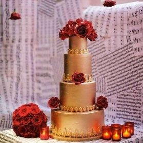 کیک چند طبقه جشن نامزدی یا عروسی با تم طلایی تزیین شده با رزهای قرمز