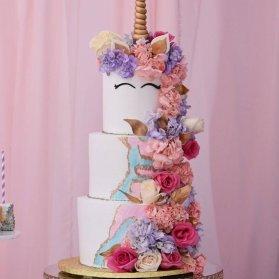 کیک چند طبقه جشن تولد دخترانه با تم اسب تک شاخ (Unicorn) تزیین شده با گل های طبیعی صورتی یاسی