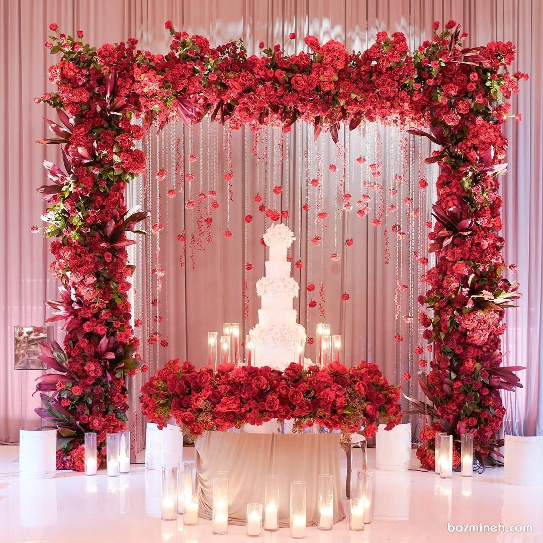 گل آرایی و شمع آرایی منحصر به فرد جایگاه کیک جشن عروسی با گل های طبیعی قرمز