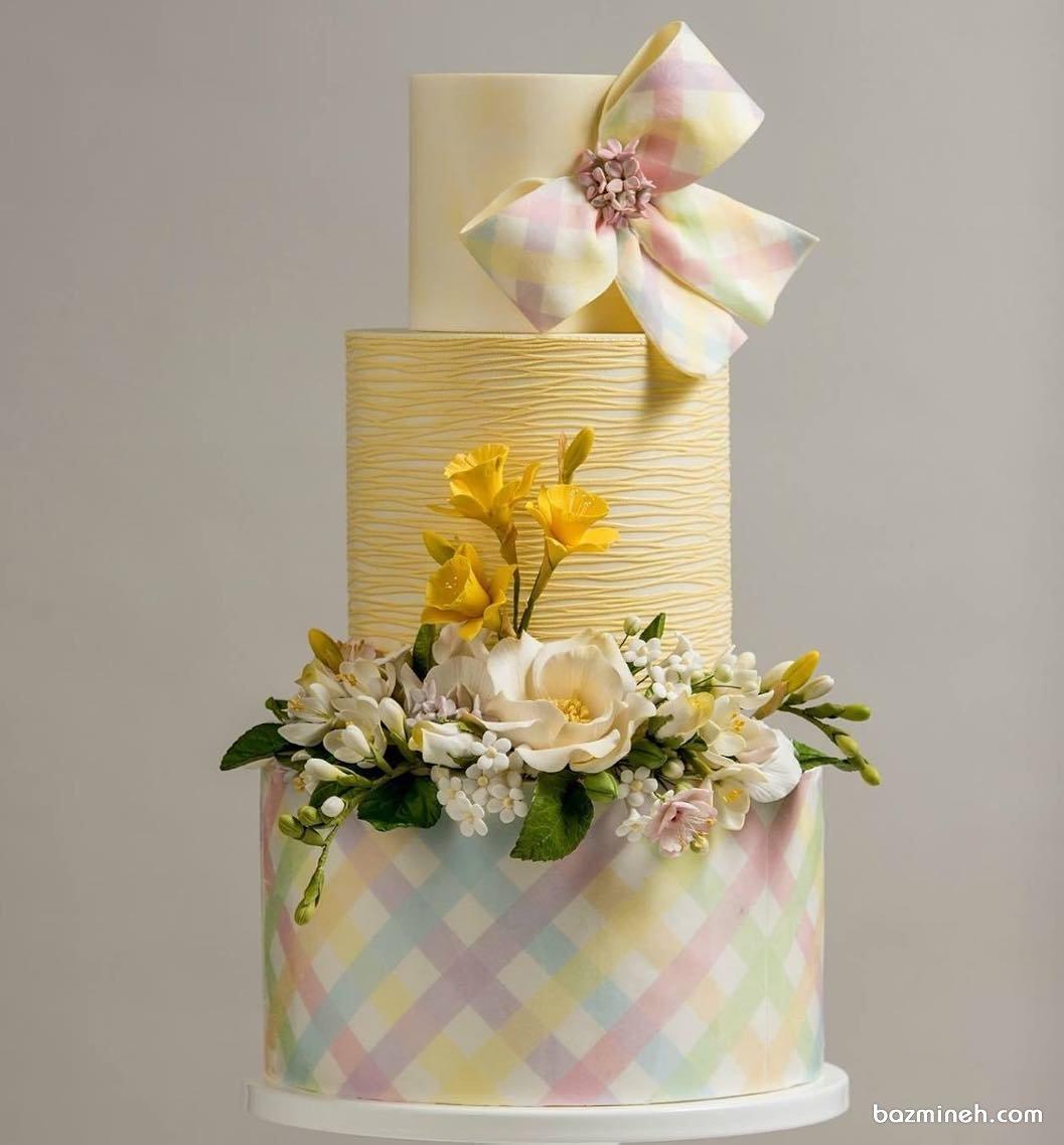 کیک چند طبقه جشن نامزدی یا سالگرد ازدواج با تم زرد تزیین شده با گل و پاپیون
