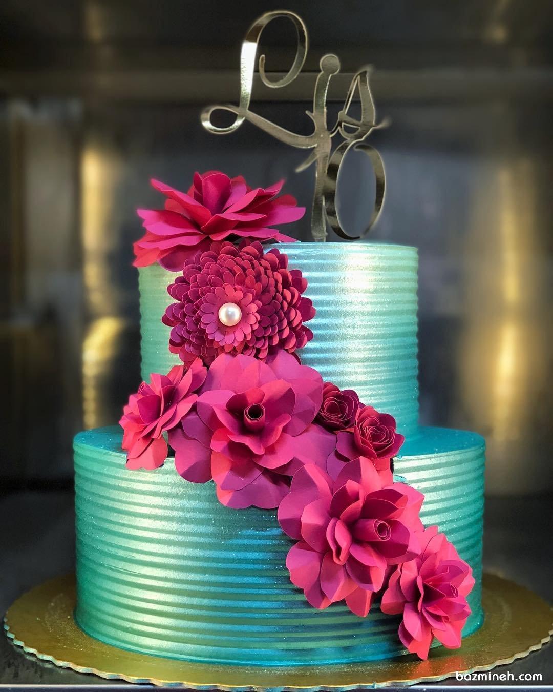 کیک دو طبقه جشن تولد تزیین شده با گل های کاغذی سرخابی