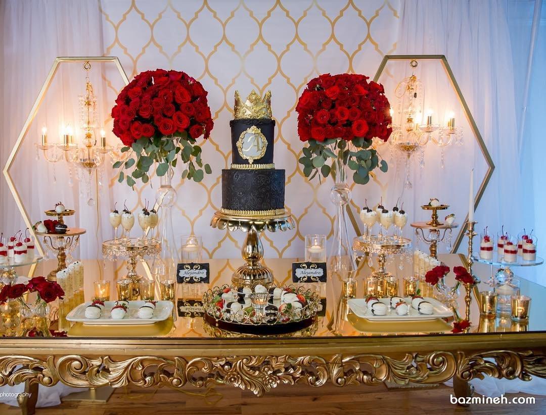 میزآرایی شیک جشن تولد بزرگسال با تم طلایی قرمز همراه با گل آرایی زیبای رزهای قرمز