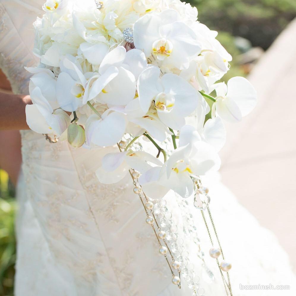 ارکیده های سفید در ترکیب با مرواریدهای زیبا جذابترین دسته گل عروس را ایجاد می کند.
