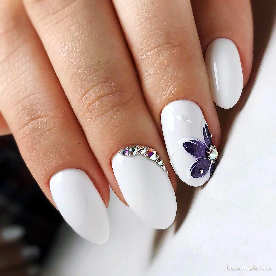 مدل کاشت ناخن گرد با لاک سفید براق و دیزاین زیبای آن با طراحی گل بنفش و نگین