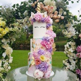 کیک چند طبقه زیبای جشن تولد دخترانه با تم اسب تک شاخ (Unicorn) تزیین شده با گل های طبیعی