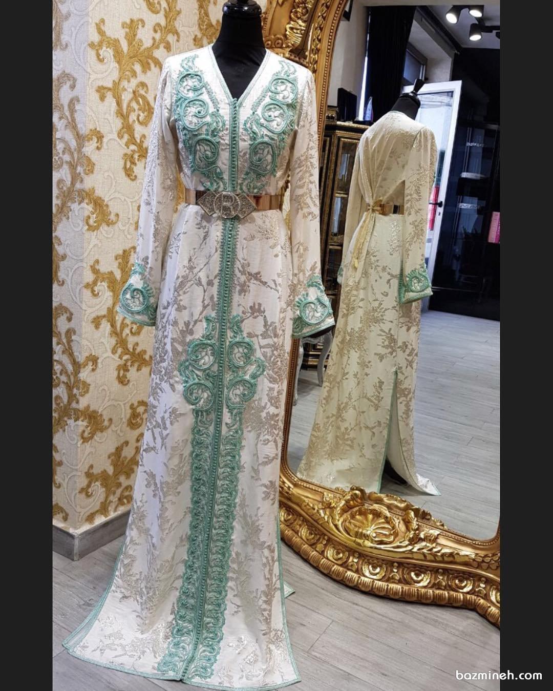 مانتو عقد بلند سفید رنگ با نوار دوزی سبز آبی و طرح های طلایی زیبای روی پارچه