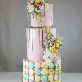کیک سه طبقه جشن تولد دخترانه با تم صورتی و ایده جالب تزئین آن با ماکارون های رنگی