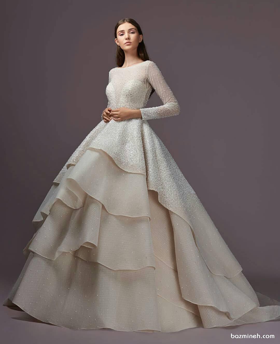 لباس نامزدی ساده و شیک پوشیده توری آستین دار مروارید دوزی شده با دامن پفی مدل طبقه ای دنباله دار