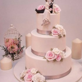 کیک چند طبقه جشن نامزدی یا سالگرد ازدواج با سبک وینتج تزیین شده با نماد عروس و داماد و گل های خمیر فوندانت