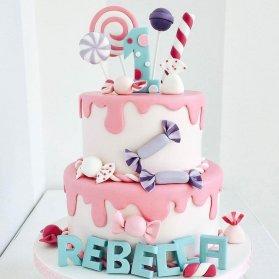 کیک فوندانت جشن تولد یکسالگی کودک با تم شکلات و آبنبات چوبی