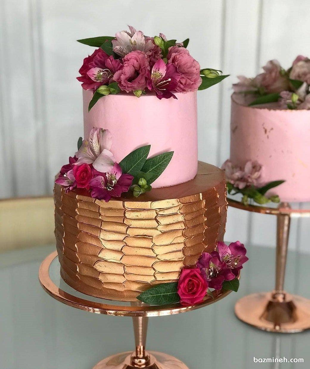 کیک دو طبقه زیبای جشن تولد بزرگسال یا سالگرد ازدواج با تم صورتی طلایی تزیین شده با گل های طبیعی