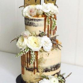 کیک دو طبقه جشن سالگرد ازدوج تزیین شده با گل های طبیعی با تم پادشاه و ملکه