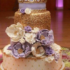 کیک چند طبقه فوندانت جشن بیبی شاور دخترونه با تم تاج سفید یاسی طلایی تزیین شده با گل های خمیری فوندانت