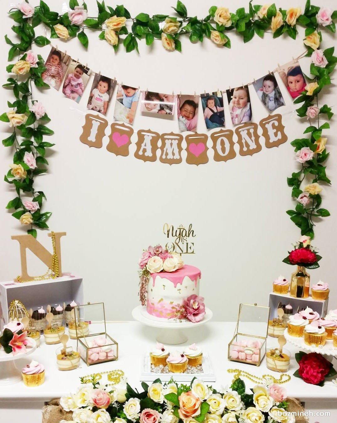 دکوراسیون ساده و زیبای جشن تولد یکسالگی دخترونه با تم سفید صورتی و ایده جالب آویزان کردن عکس های کودک در ماه های مختلف