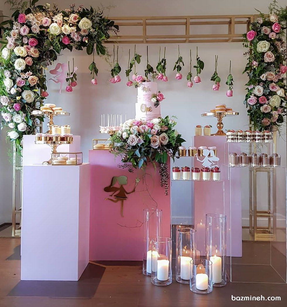 دکوراسیون رمانتیک جشن تولد دخترونه با تم فرشته صورتی همراه با گل آرایی زیبای رزهای طبیعی صورتی کرم و شمع آرایی