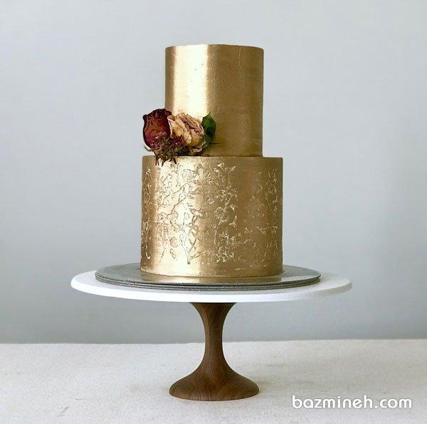 کیک دو طبقه جشن تولد یا سالگرد ازدواج با روکش طلایی با تزیین خاص گلهای خشک شده