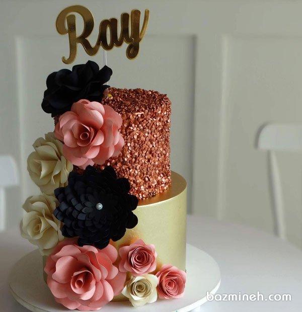 کیک دو طبقه جشن تولد بزرگسال با تم گلبهی طلایی مشکی و تزیین زیبای گلهای کاغذی