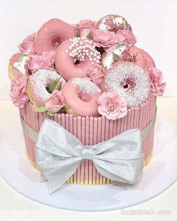 کیک زیبای جشن تولد بزرگسال یا سالگرد ازدواج با تم صورتی نقره ای و تزیینات دونات های روکشدار رنگی