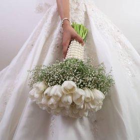 دسته گل زیبای عروس با گل های لاله سفید رنگ بسته شده با تور مروارید دوزی شده
