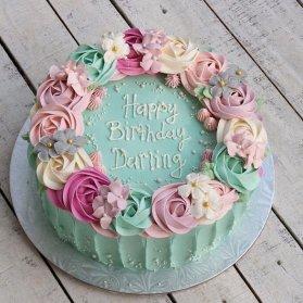 کیک خامهای جشن تولد بزرگسال تزیین شده با گلهای خامهای