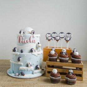 کیک دو طبقه فوندانت جشن تولد کودک همراه با کاپ کیک های شکلاتی عروسکی با تم پنگوئن ها