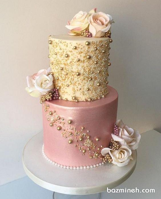 کیک دو طبقه جشن نامزدی یا سالگرد ازدواج با تم صورتی طلایی تزیین شده با گلهای رز طبیعی و مرواریدهای خوراکی