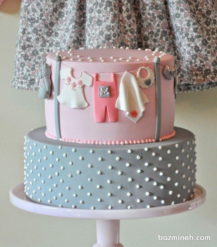 کیک دو طبقه فوندانت جشن بیبی شاور دخترونه با تم طوسی صورتی