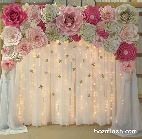 ایده خلاقانه دکوراسیون جشن تولد دخترونه تزیین شده با گلهای کاغذی و ستارههای طلایی