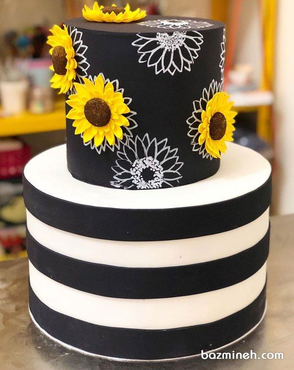 کیک دو طبقه فوندانت جشن تولد بزرگسال یا سالگرد ازدواج با تم سفید مشکی و گلهای آفتابگردون