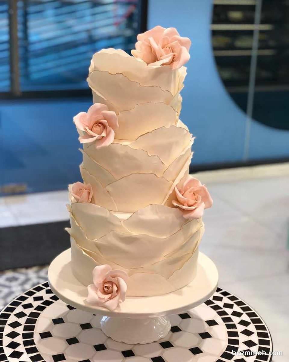 کیک چند طبقه خامهای جشن نامزدی یا سالگرد ازدواج تزیین شده با گلهای فوندانت گلبهی