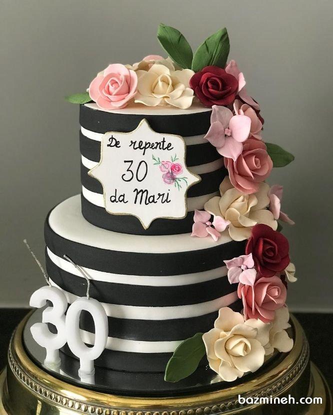 کیک دو طبقه فوندانت جشن تولد بزرگسال با تم سفید مشکی و گلهای خمیری فوندانت رنگی