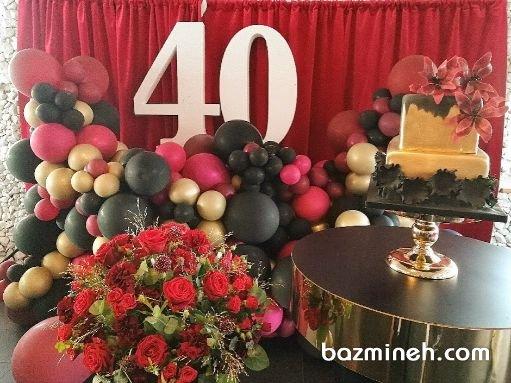 دکوراسیون 40 سالگی با رنگهای گرم همراه با کیک طلایی و مشکی و استند عدد