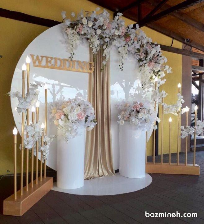 دکوراسیون و گل آرایی جایگاه عروس و داماد در جشن نامزدی و عروسی با تم رنگی سفید طلایی تم سفید و طلایی از جمله رنگ بندی های بسیار زیبا و شیک و مناسب برای مراسم عروسی، نامزدی و عقد می باشد که به خوبی بیانگر شکوه اینگونه از مراسم هاست. گل آرایی و استفاده از شمع آرایی و میزهای متفاوت بسیار توصیه می شود.