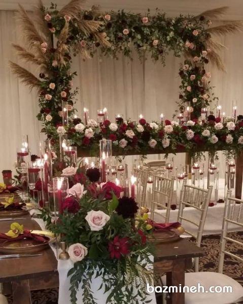 دکوراسیون و گل آرایی جایگاه عروس و داماد در جشن نامزدی با تم رنگی کرم قرمز