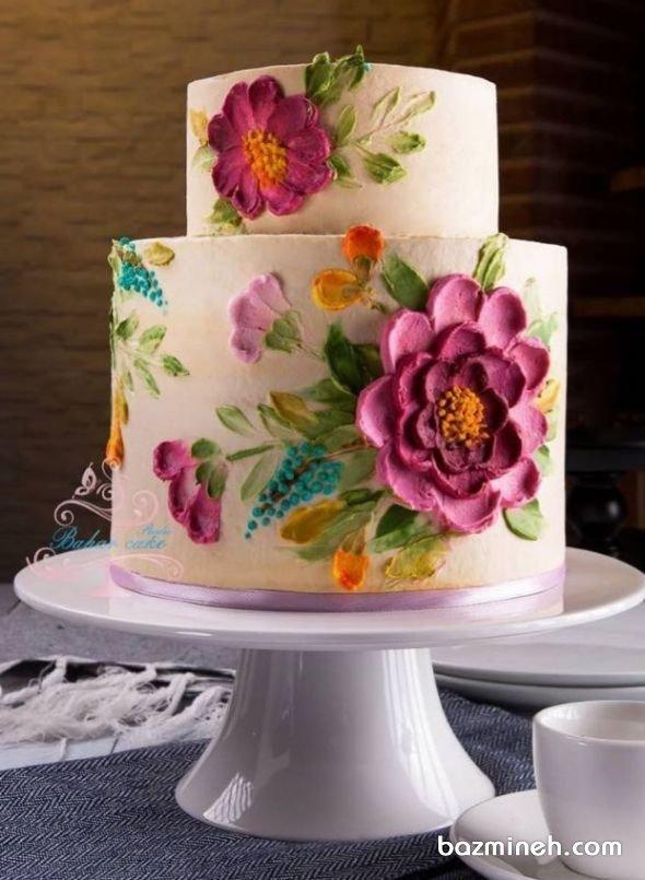 کیک دو طبقه جشن تولد بزرگسال با تزیین گلهای خامهای نقاشی روی کیک یکی از زمینه های بسیار هنرمندانه در صنعت دکوراسیون کیک است که بیشتر در کیک تولد بزرگسال و کیک های عروسی و کیک عقد و کیک نامزدی کاربرد دارد. در این ایده تلفیق رنگ های شاد و روشن را در نقاشی روی کیک دو طبقه میبینید.