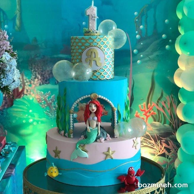 کیک چند طبقه جشن تولد دخترونه با تم پری دریایی یکی از رنگ هایی که با دیزاین پری دریایی برای تولدهای دخترانه همخوانی دارد، رنگ آبی فیروزه ای یا سبزآبی است که جلوه ای بسیار جذاب به تولد می دهد. رنگ آبی فیروزه ای نماد ارامش و خوش شانسی است که انتخاب ان برای تولدهای دخترانه بسیار بجاست
