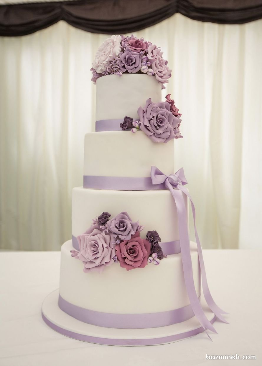 کیک چند طبقه رمانتیک جشن نامزدی و عروسی با تم رنگی سفید یاسی  اگر از علاقمندان به رنگ یاسی و بنفش هستید این کیک زیبای نامزدی و عقد را به تامین کنندگان بزمینه سفارش دهید تا با تزئین گل های شکری و فوندانتی به همراه رنگ بنفش، جشن رمانتیکی را برای خود رقم بزنید.