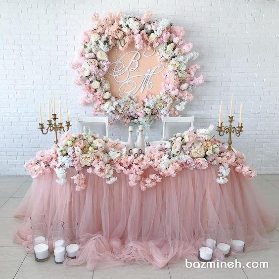 دکوراسیون و گل آرایی یونیک جشن بله برون یا نامزدی با تم رنگی صورتی سفید از جمله دکواسیون هایی است که برای میزهای نامزدی و مراسم های عقد و بله برون توصیه می شود و فضایی رمانتیک و زیبا را به وجود می آورد. تزئینات نامزدی و عقد با تور و گل های طبیعی و گل ارایی با روش های مدرن و ریسه ای بسیار پرکاربرد هستند که می توانند متناسب با رنگ لباس عروس خانم انتخاب شوند.